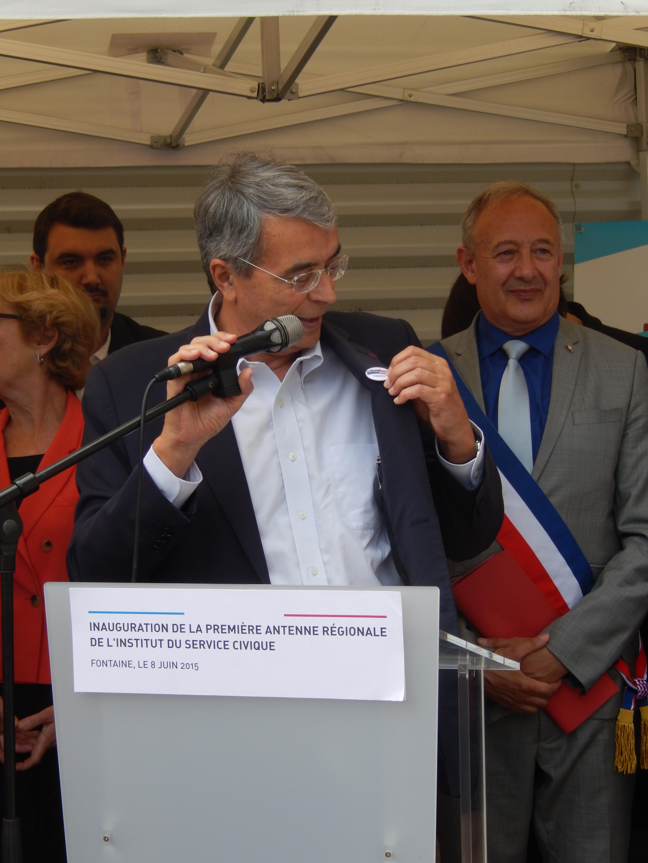 Jean-Jack Queyranne arbore le « badge» de l'Institut du Service Civique. La Région soutient depuis son lancement le projet d'implantation régionale.